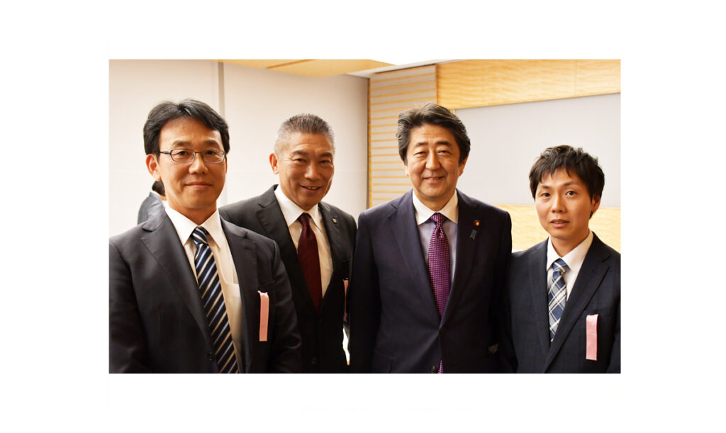 安倍総理と記念撮影するシグマ株式会社代表と社員